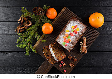 Flatlay of tasty homemade fruit cake with candied fruits, clementines, star anise, cinnamon and fir branch on black background