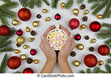 Female hands holding a cup with marshmallow. Christmas composition made of gold and red balls for a Christmas tree, and fir branches. Winter flat lay.