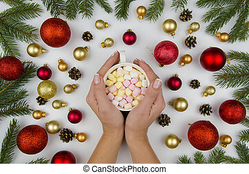 Christmas composition made of gold and red balls for a Christmas tree, cones and fir branches. Female hands holding a cup with marshmallow. Winter flat lay