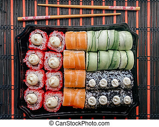 Flatlay photography of roll set on a table with chopsticks for sushi. Home delivery, Japanese sushi rolls.