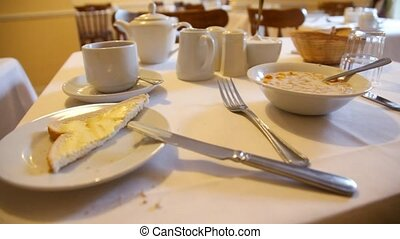 flatware and corn flakes with milk on table in cafe