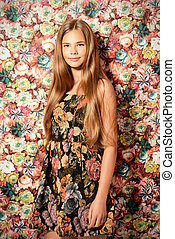 Smiling girl teenager posing in summer dress by a floral background. Beauty, fashion.