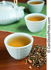 Flavored green tea - Teapot and cups filled with flavored...
