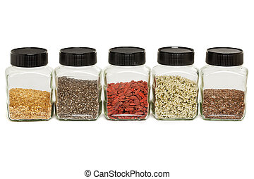 flax, chia, hemp seeds and goji - row of glass jars with ...