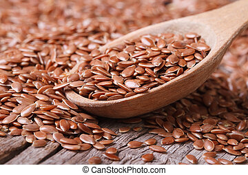 Flax seeds close up on a wooden spoon on a table