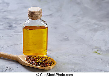 Flax seeds in scoop and flaxseed oil in glass bottle on light textured background, top view, close-up, selective focus