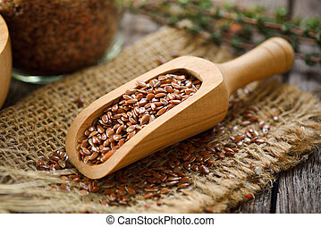 Flax seeds in wood scoop on table