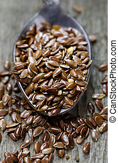 Flax seeds on a spoon. Wooden background