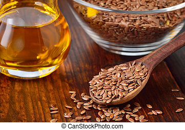 Flaxseeds and linseed oil. - Brown flax seeds on spoon and...