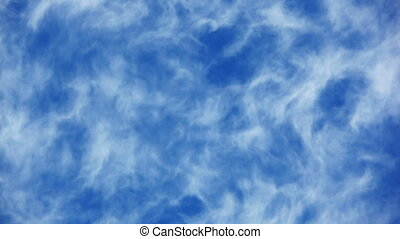Fleecy clouds passing accelerated throw blue sky background
