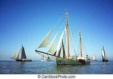 Fleet of traditional sailing ships - Blue color image of a...