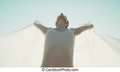 Flexible beautiful woman - dancer stands on rock and opens silk fabric like wings. Flap of cloth flutters in the wind. Nature, freedom concept. Slow motion. High quality FullHD footage