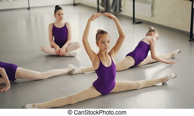 Flexible children ballet dancers doing stretching exercises...