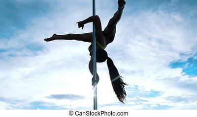 Flexible female pole-dancer in sports lingerie exercising on...