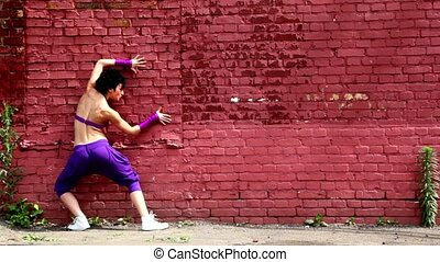 Flexible girl dances near red brick wall at summer day