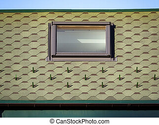 Flexible green tiles with basalt granulate in the form of hexagons cover the roof of the house. There is a window in the attic. Construction abstract background with tiles and window.