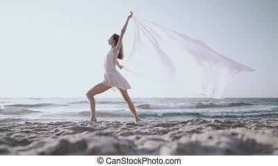 Flexible gymnast is dancing on ocean with huge silk fabric ...