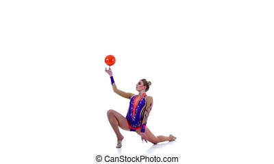 Flexible gymnast leads the ball on his body. White background. Slow motion