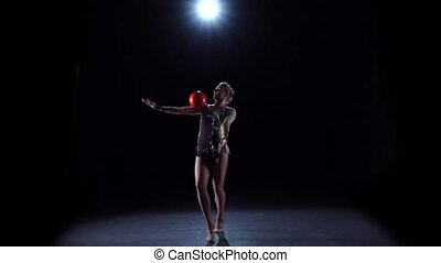 Flexible gymnast leads the ball on his body. Black background. Slow motion. Light rear