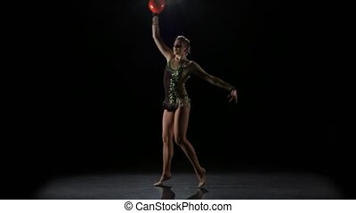 Flexible gymnast leads the ball on his body. Black background