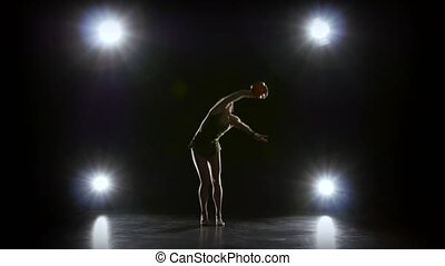 Flexible gymnast leads the ball on his body. Black background. Light rear