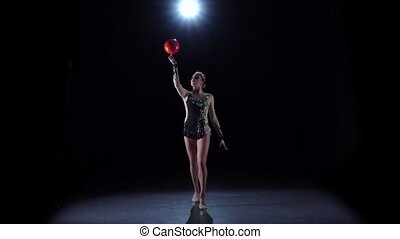 Flexible gymnast with ball creates beautiful hands graceful movements. Black background. Slow motion