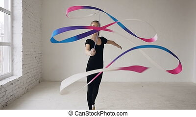 Flexible gymnast with colored tape creates beautiful and graceful movement in indoor in white background and looking at the camera. Rhythmic gymnastics: Girl training a gymnastics exercise with a ribbon
