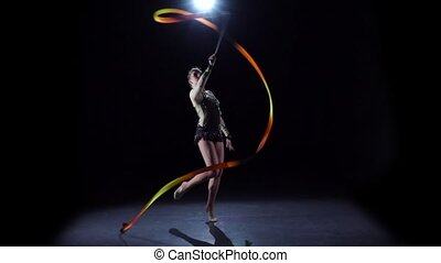 Flexible gymnast with tape creates beautiful hands graceful movements. Black background. Slow motion