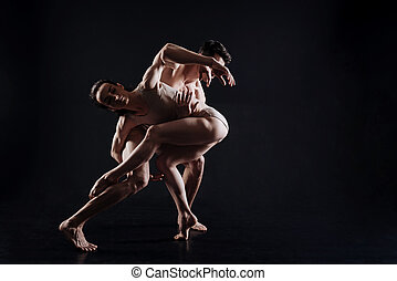 Flexible gymnasts performing in the black colored studio