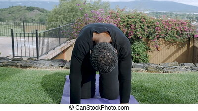Flexible healthy retired African American woman doing cat cow yoga pose