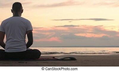 Flexible man in lotus pose meditating on the beach