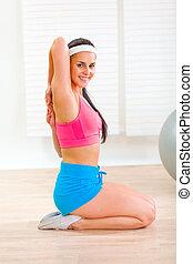 Flexible slim female doing gymnastics exercise at home