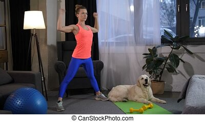 Flexible woman doing sports with dog at home