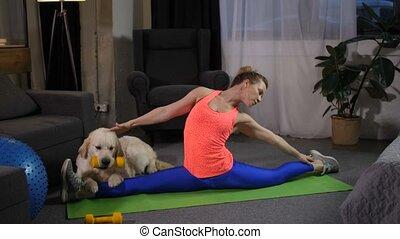 Flexible woman doing stretching sitting on split - Gymnast...