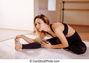 Flexible woman stretching her right leg in gym.