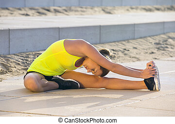 Flexible woman stretching on a beach boulevard - Young,...