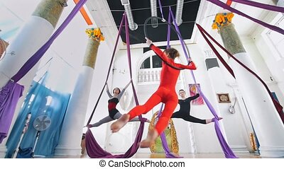 Flexible women air gymnasts makes a gymnastic elements in...