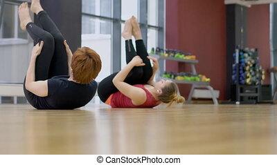 Flexible women is practicing yoga in modern studio.