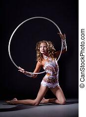 Flexible young girl posing with gymnastic hoop