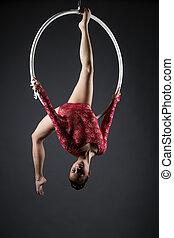 Flexible young girl with hoop posing head down