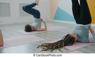 Flexible young people in sportswear are practiising reverse yoga position on mats in modern sports center. Well-being, healthy lifestyle and active hobby concept.