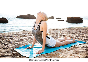 Flexible young woman doing stretching yoga exercises