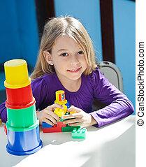 flicka, sittande, med, toys, på skrivbordet, in, förskola