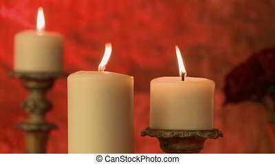 Flickering flame of candles on red background