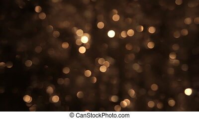 Flickering of gold tinsel is out of focus. Christmas...