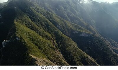 fligh over green mountains - aeraial view of green mountains