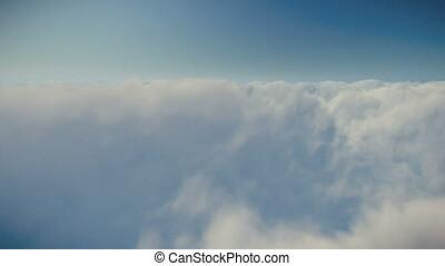 Flight above clouds against blue sky, 4K