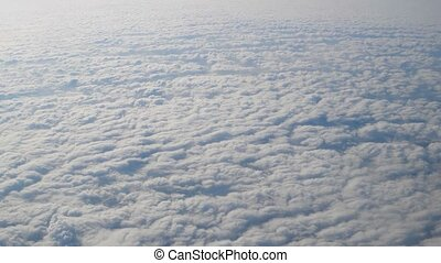 Flight above clouds natural view from side window of airplane