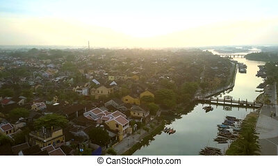 flight above river with bridges boats in ancient town Hoian