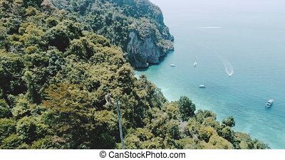Flight above the trees and Andaman sea on Phi Phi island,...